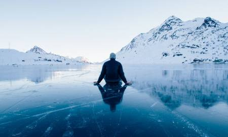man-sitting-on-a-frozen-lake-looking-at-mountains