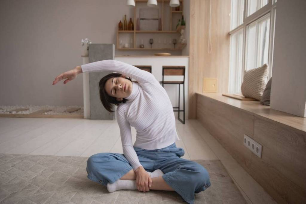 A woman doing a relaxing yoga pose at home